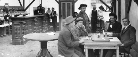 "Four men sit around a table playing cards (right foreground). Several people are gathered around one end of a bar (left), including two children sitting on the bar. A barber is set up in the corner with the tools of his trade. Legible signs include: ""Pabst Bohemian"", ""Wagon covers, awnings, made by hand or machine, tents for rent, [...] all kinds [...] of canvas, 136 S. Main St., Los Angeles, Cal."", calendar by ""Elcelsior Soda Works [...] Los Angeles, Cal."", ""Pabst B Milwaukee"", ...""ill[...]e the Barbi""...."